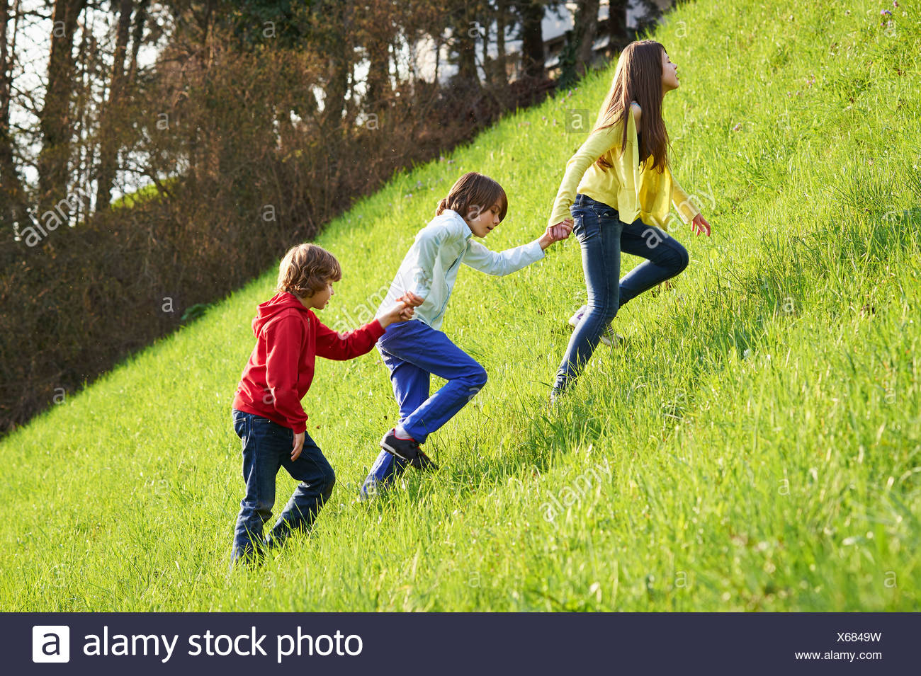 Sister and younger brothers climbing up grassy field - Stock Image