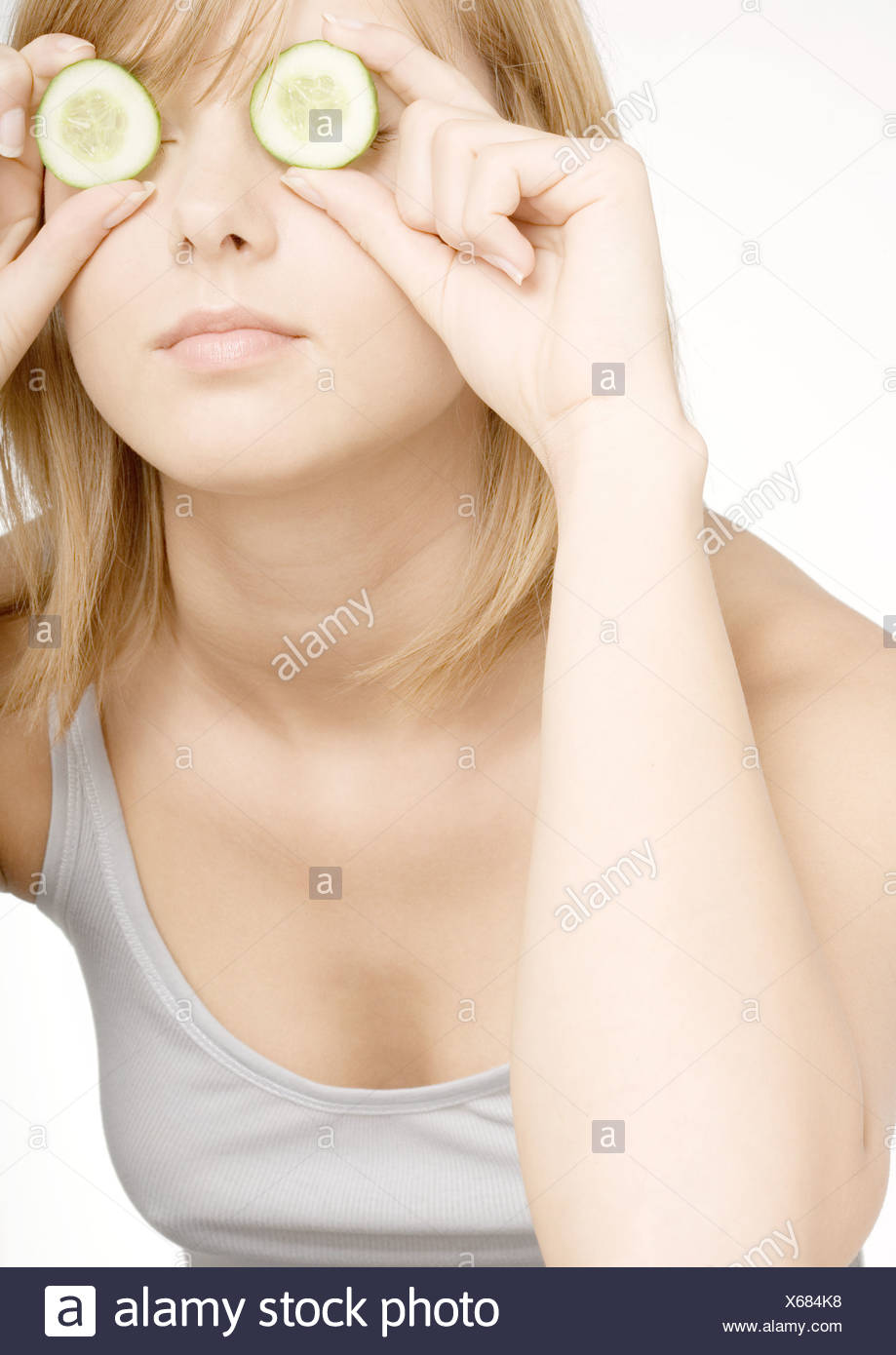 Young woman holding up cucumber slices in front of eyes - Stock Image