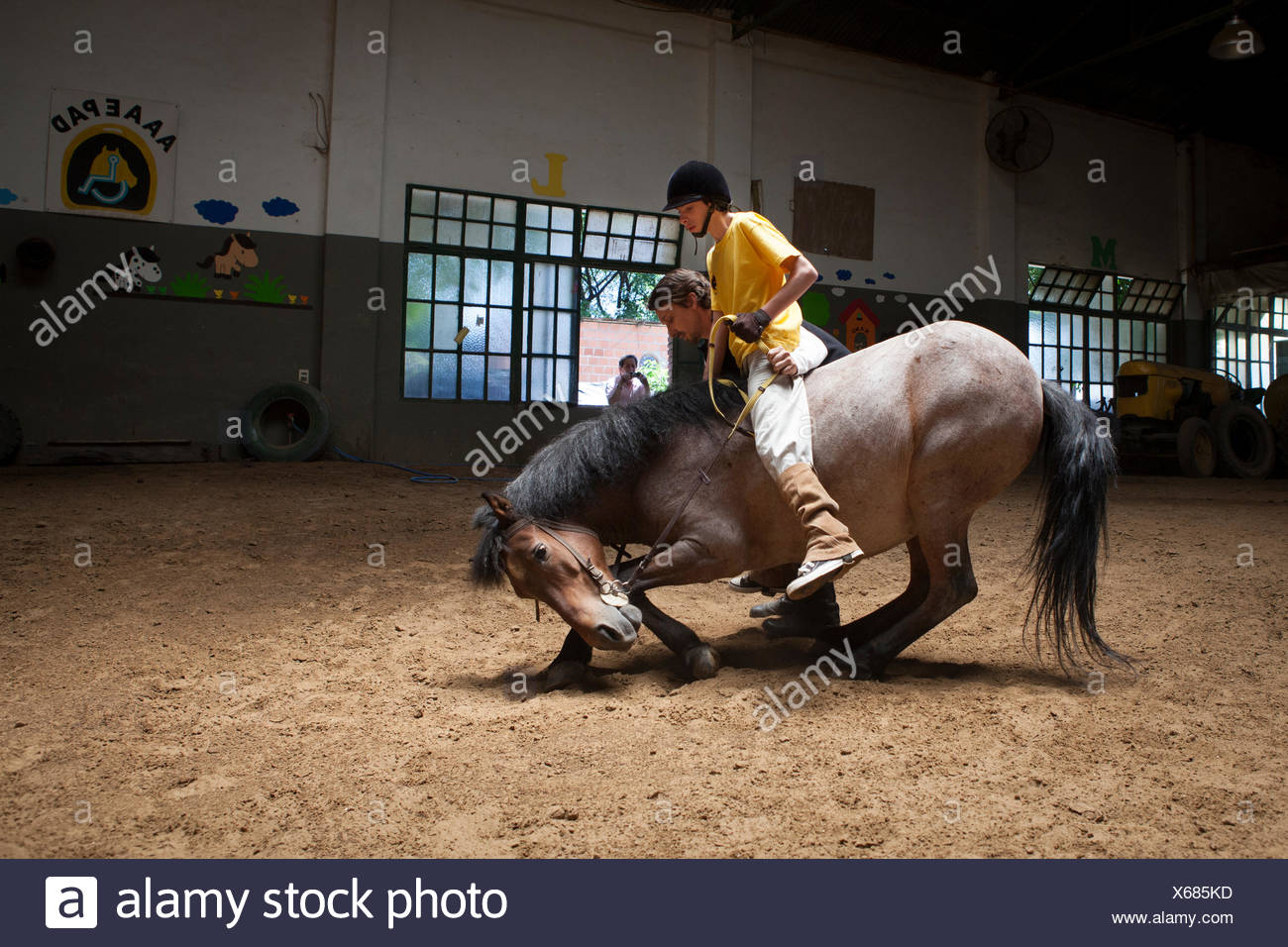 Child performing a balancing act on a horse lying Emmanuel 13 years with cerebral palsy comes to the center every week for 7 years. He now works three pillars of riding Assisi Balance and Jump. Equitherapy in partnership with the AAAEPAD Association and A - Stock Image