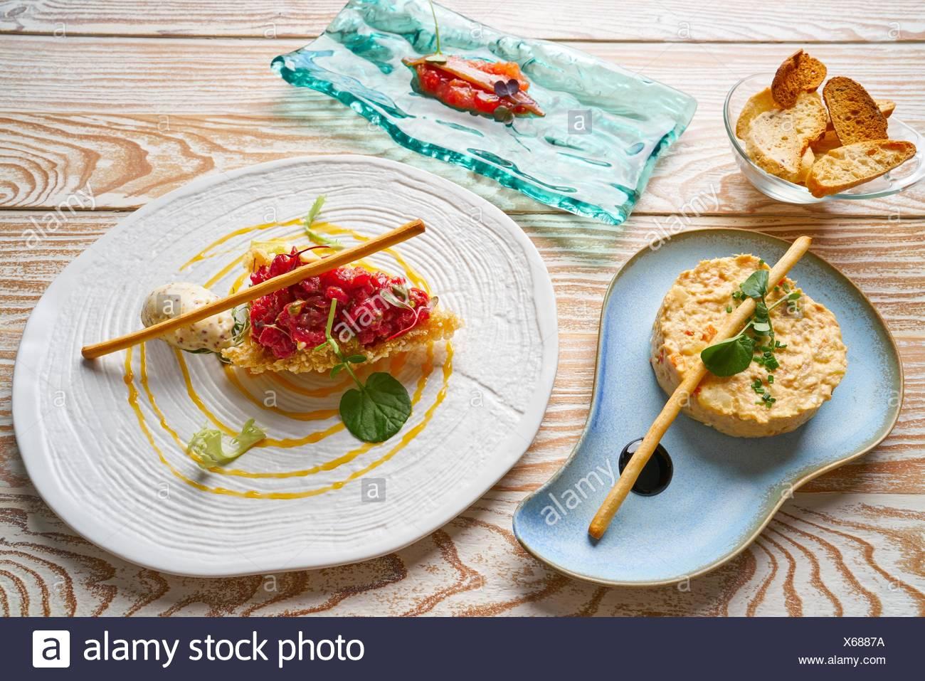 food starters potato salad Steak tartare and Anchovies with tomato Tapas. - Stock Image