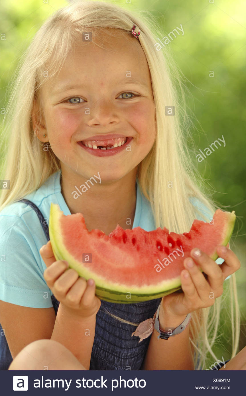 Girls, blond, watermelon, eat, there, smile, tooth gaps, portrait, model released, people, child portrait, fruit, fruit, melon, garden, summer, outside, nutrition, healthy, juicy, childhood, bite, cogs, second dentitions, gaps, happy, - Stock Image