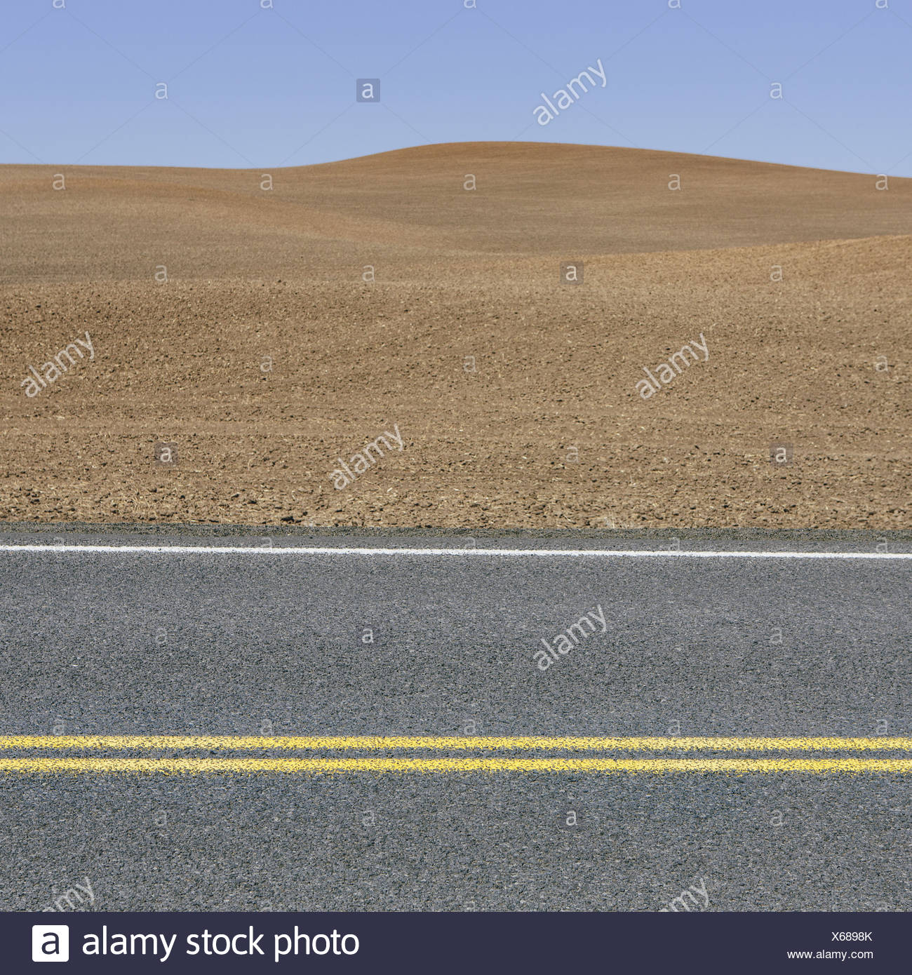 A road through the farming landscape of ploughed fields and farmland near Pullman, Washington state. Stock Photo