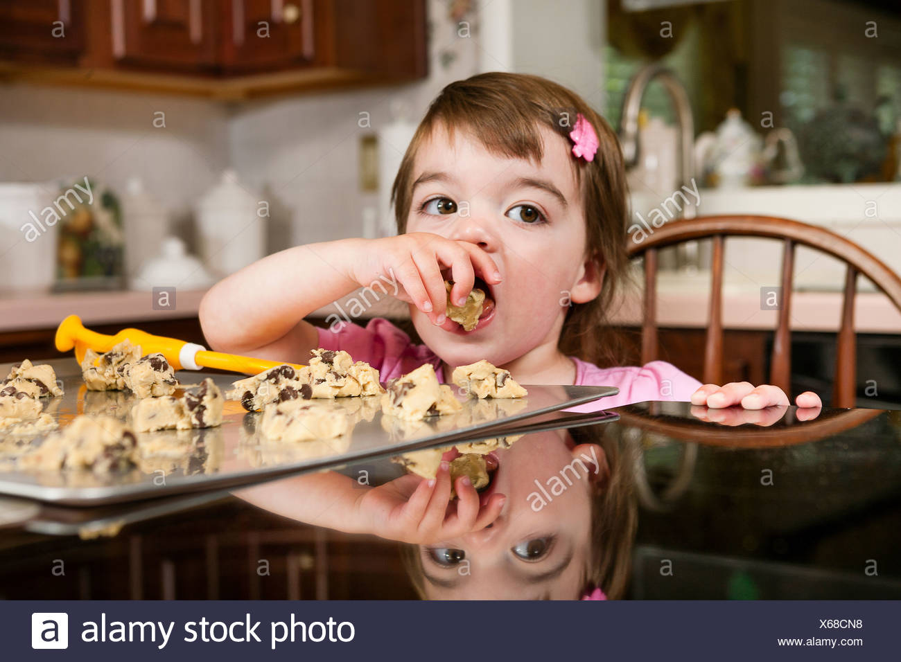 Close up portrait of young female toddler eating currant cakes - Stock Image