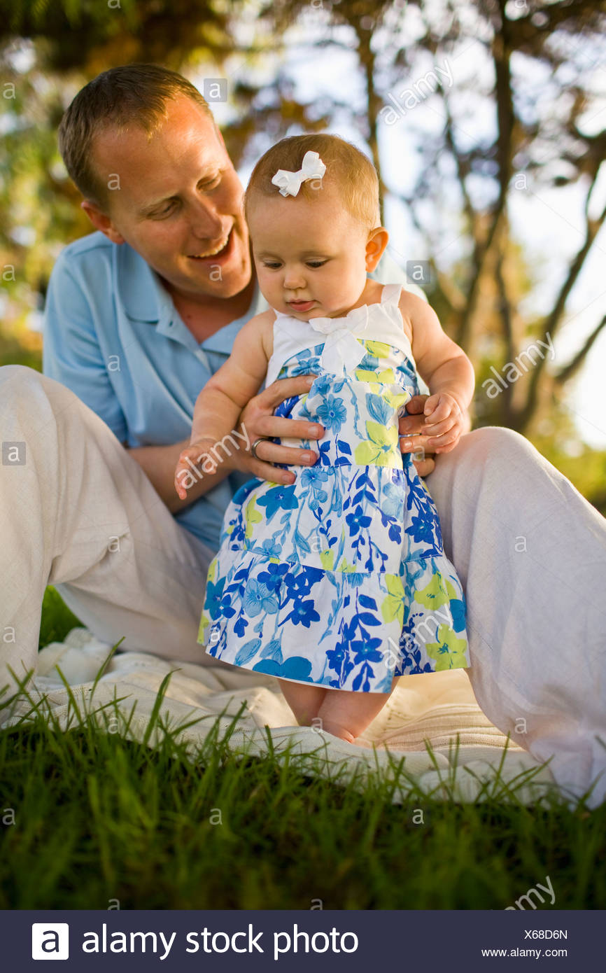 A father plays with his baby girl, while sitting on a picnic blanket outside on a sunny day in California. - Stock Image