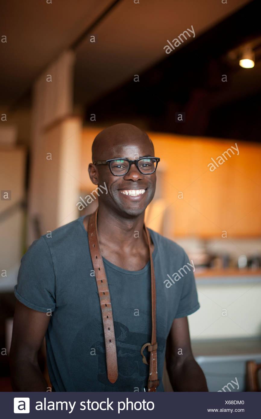 Smiling man wearing belt around neck - Stock Image