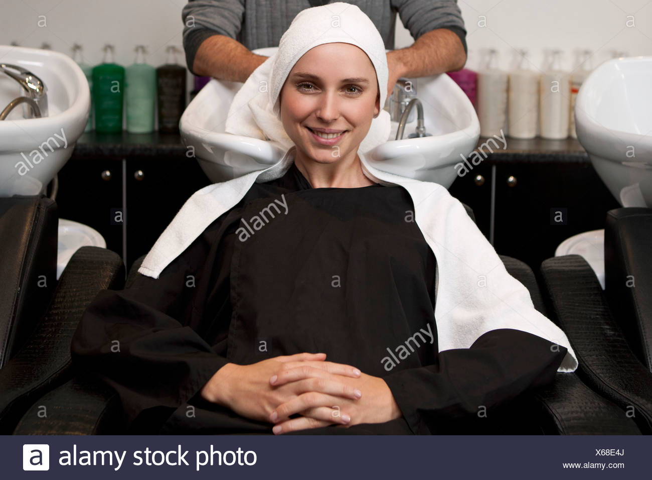 A female client sitting at a wash basin in a hairdressing salon - Stock Image