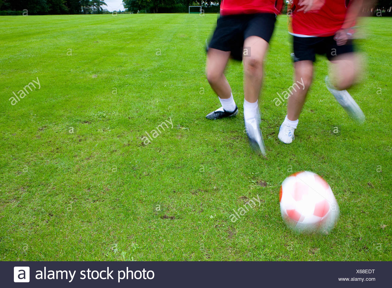 Soccer players running toward ball - Stock Image