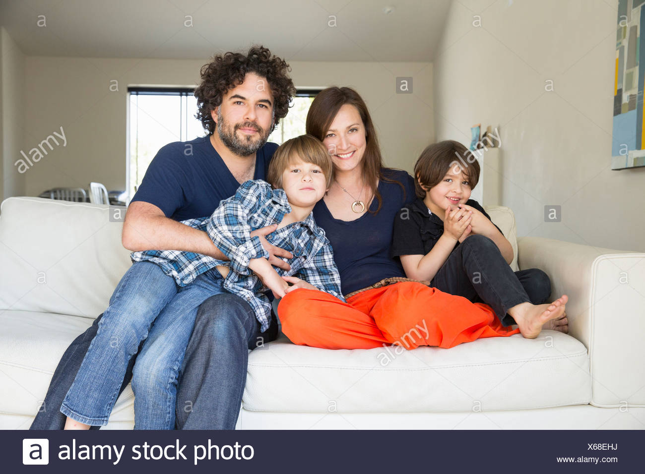 Portrait of family with two boys on sofa - Stock Image