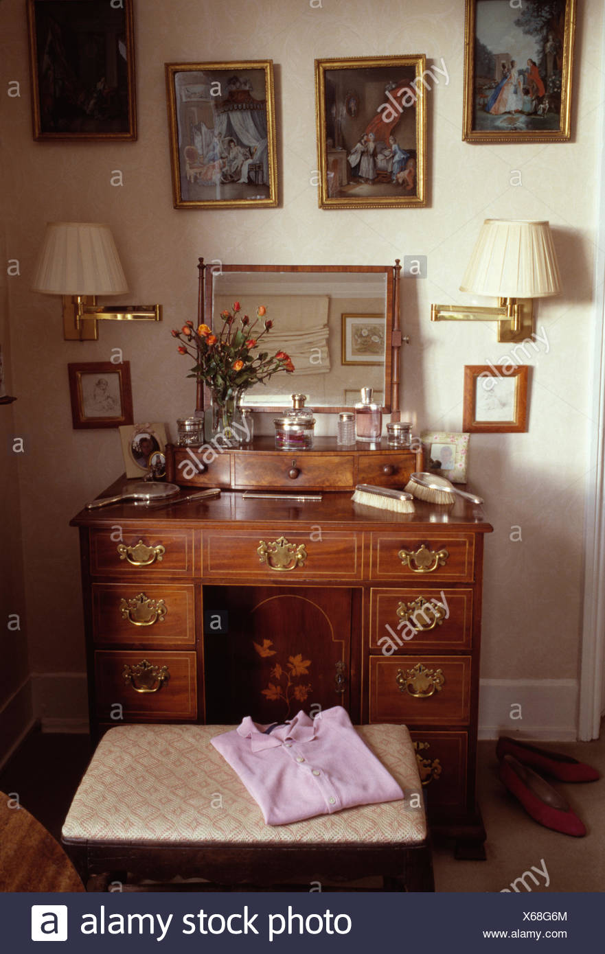 Pictures And Brass Wall Lights Above Antique Dressing Table And Stool In Cottage Bedroom Stock Photo Alamy