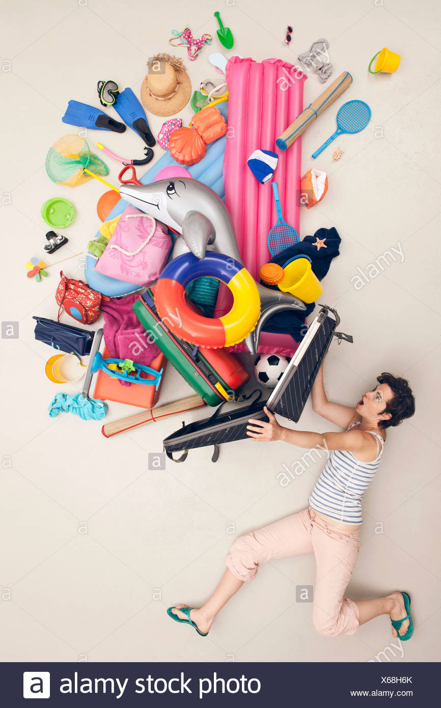 Germany, Artificial scene with woman opening baggage full of beach toys - Stock Image