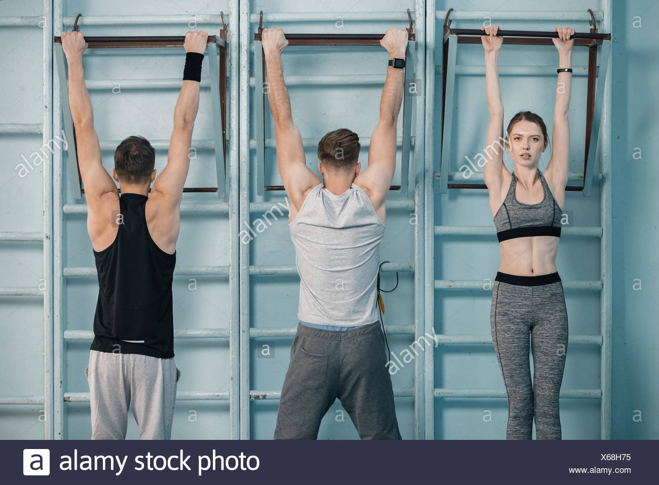 sporty men and woman hanging on sport equipment in gym - Stock Image