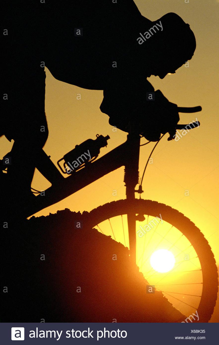 Silhouette of person mountain biking - Stock Image