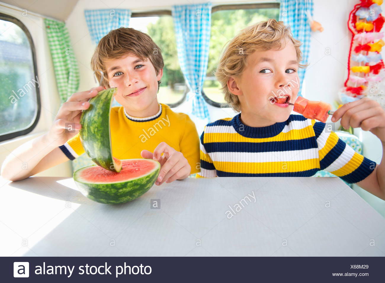 Boys eating watermelon in caravan, portrait - Stock Image
