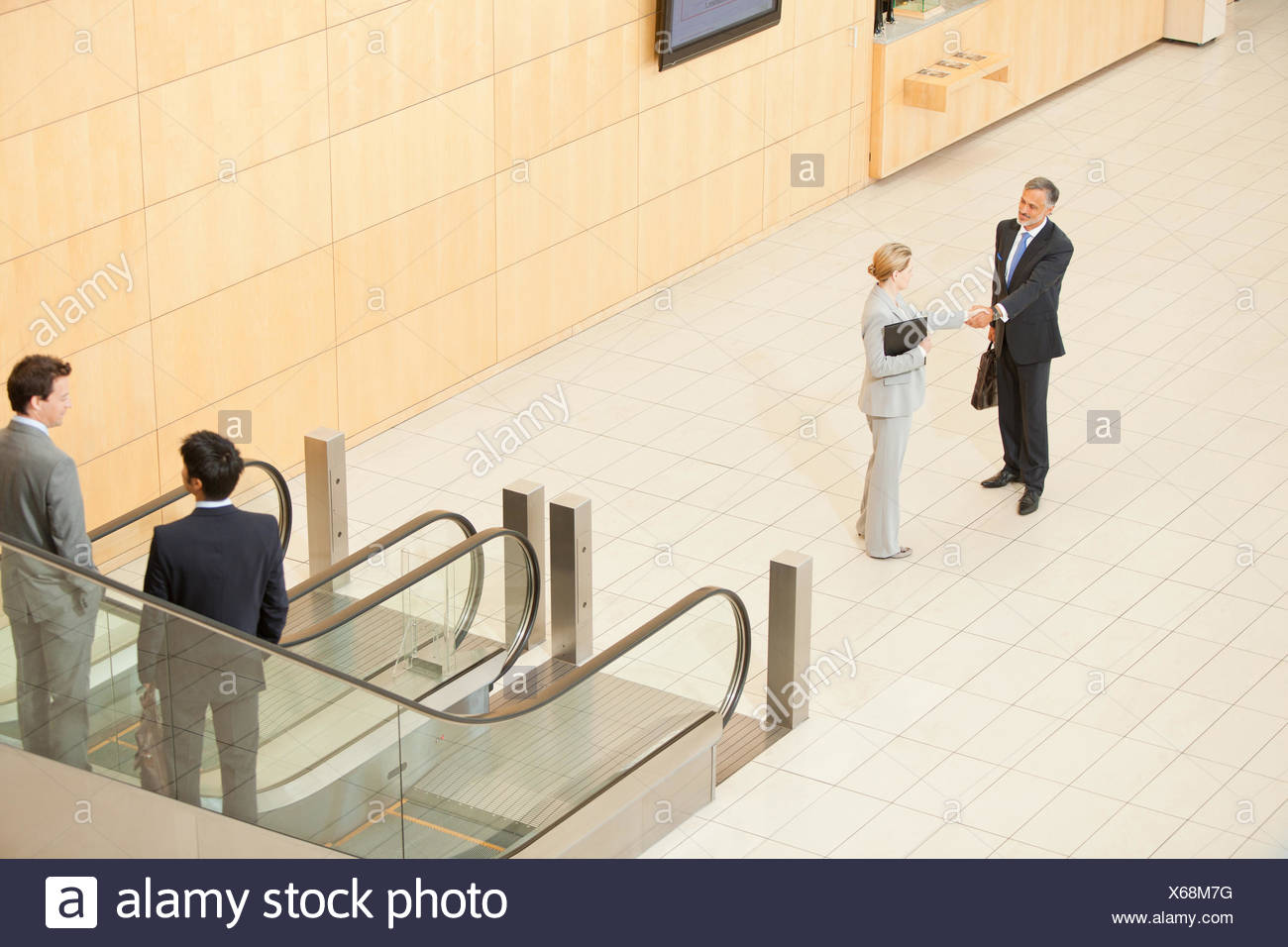 Business people standing at bottom of escalator Stock Photo