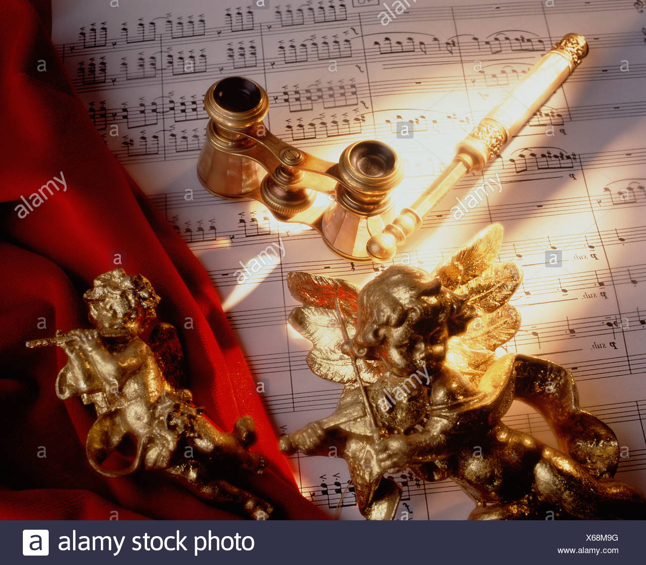 Still life. Music concept with sheet music, opera glasses, gilt cherub figures and conductor's baton. - Stock Image