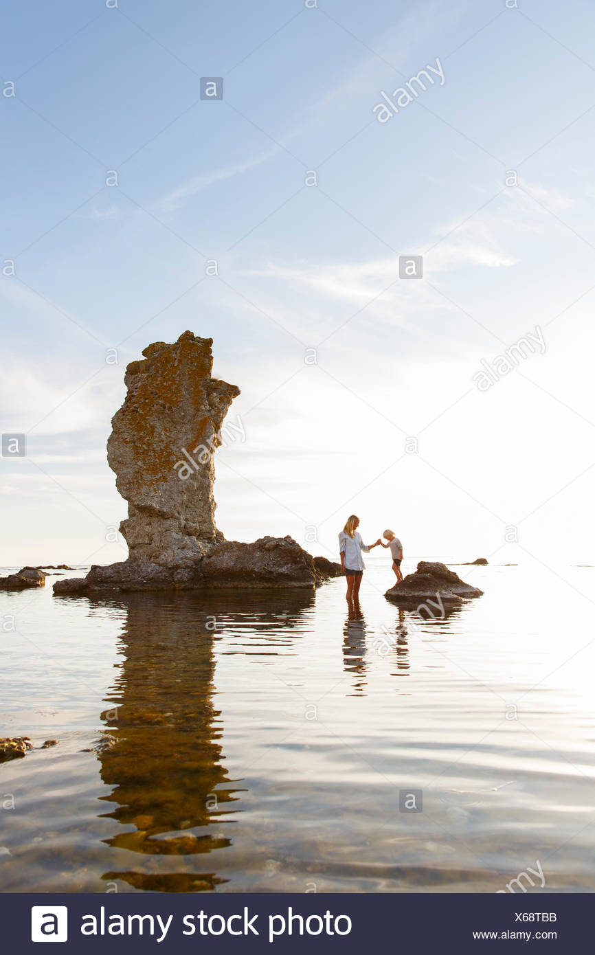 Sweden, Gotland, Faro, Mother with son (2-3) standing among rocks on Baltic Sea - Stock Image