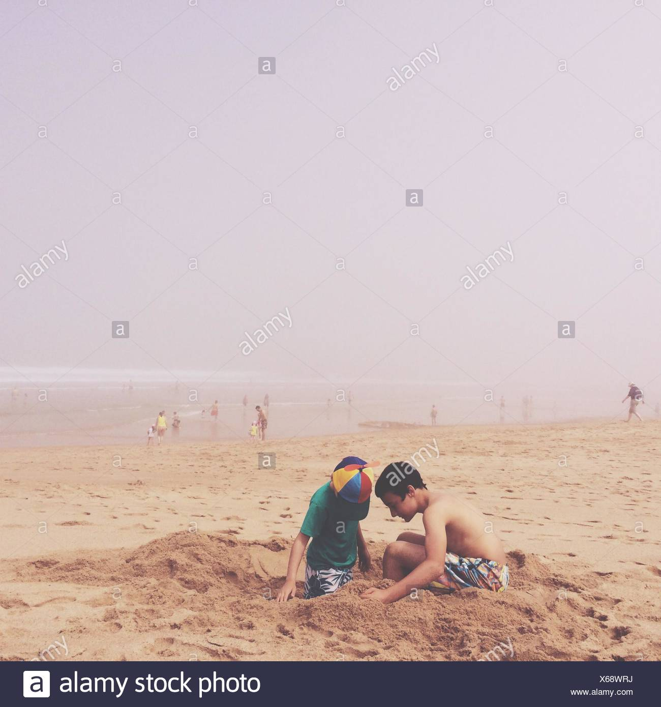 Two Boys Playing With Sand On Beach - Stock Image