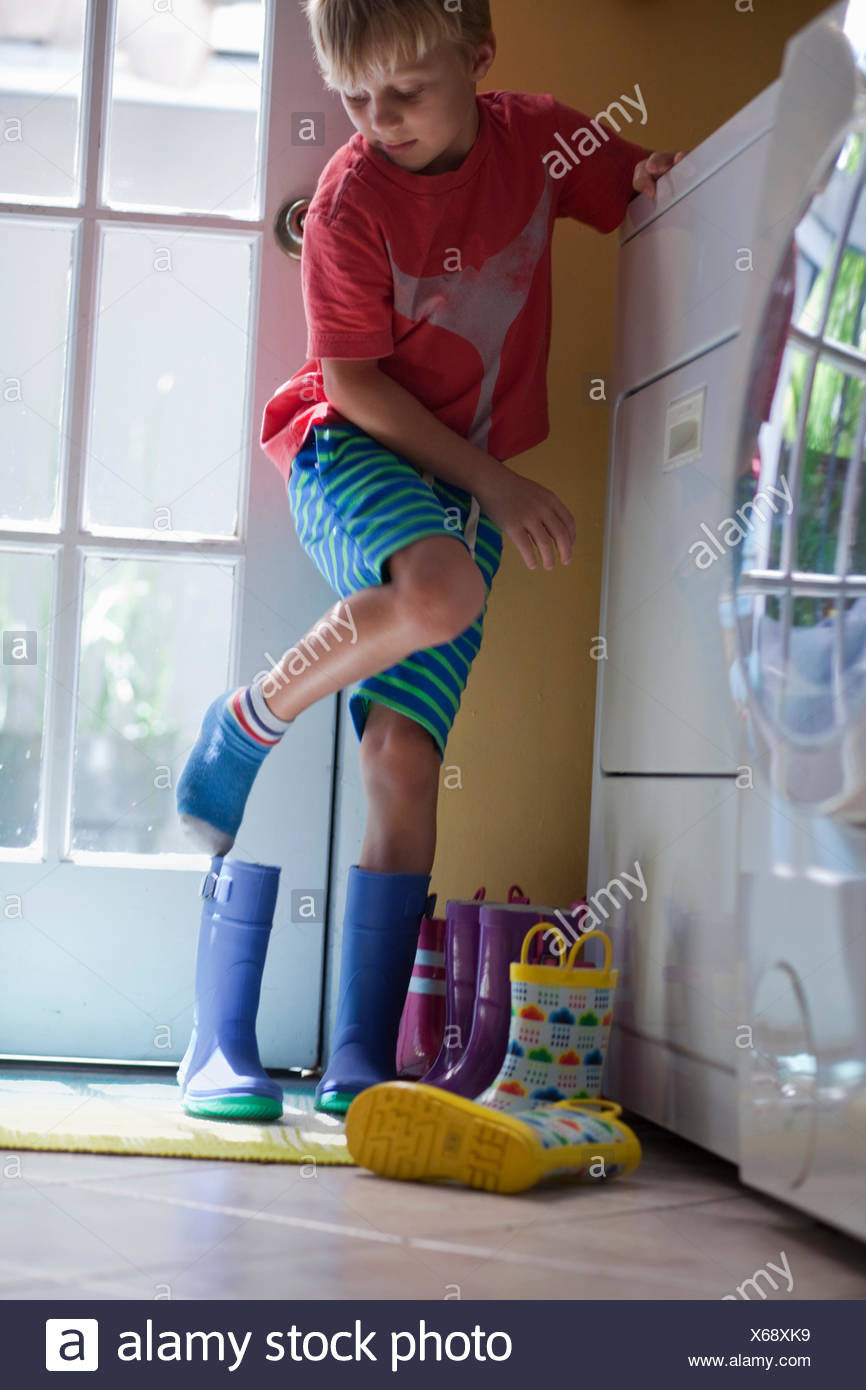 Boy putting on rubber boots at back door - Stock Image