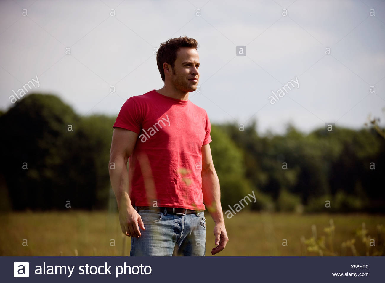 A young man standing in a field in summertime - Stock Image