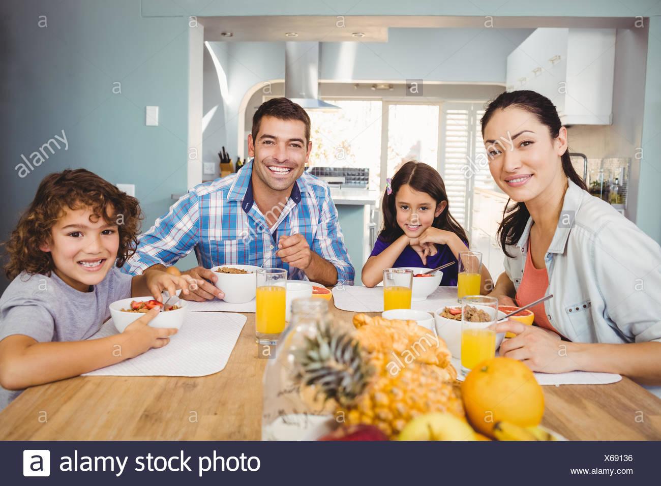 Portrait of happy family having breakfast - Stock Image