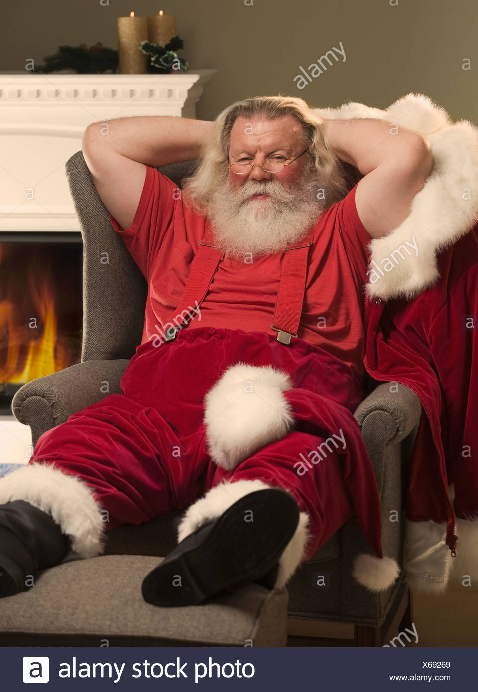 Santa Claus relaxing in armchair - Stock Image
