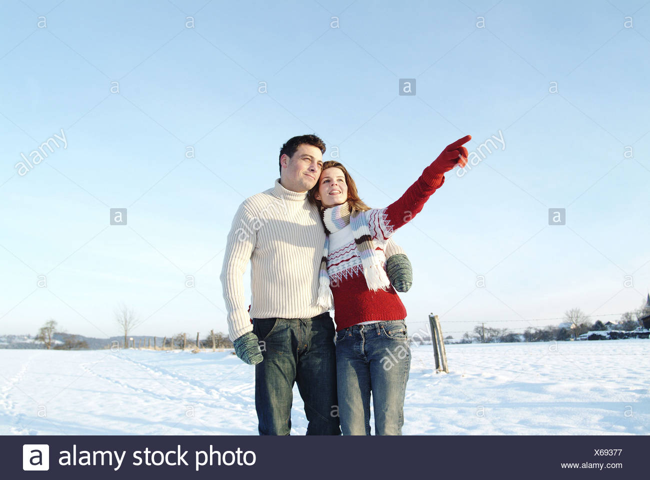 Mate young falls in love cheerfully woman gesture interprets gaze distance walk winter-landscape people two 30-40 years - Stock Image
