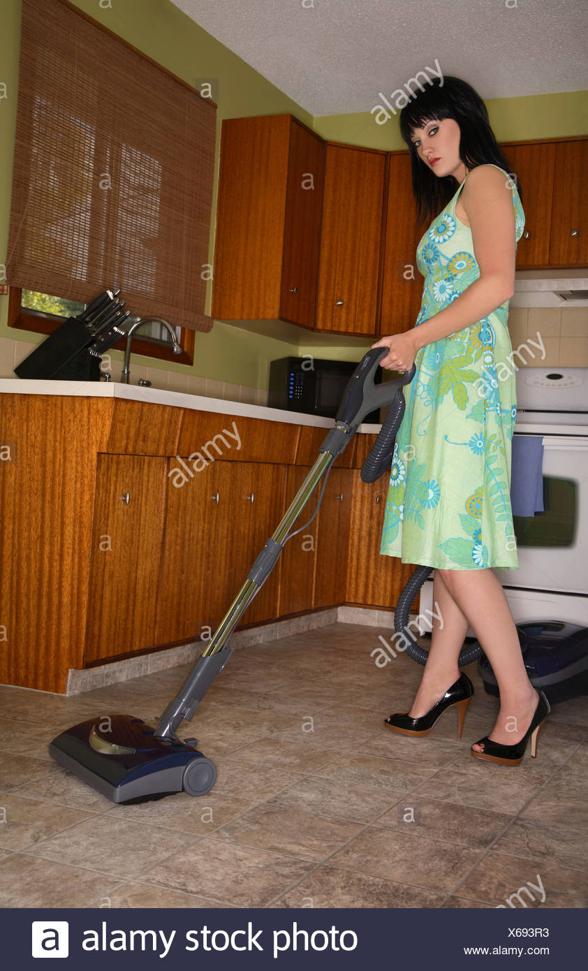 1970s style woman using vintage floor sweeper in kitchen - Stock Image