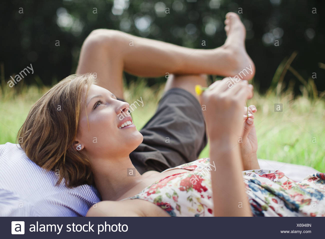 Couple laying in field together - Stock Image