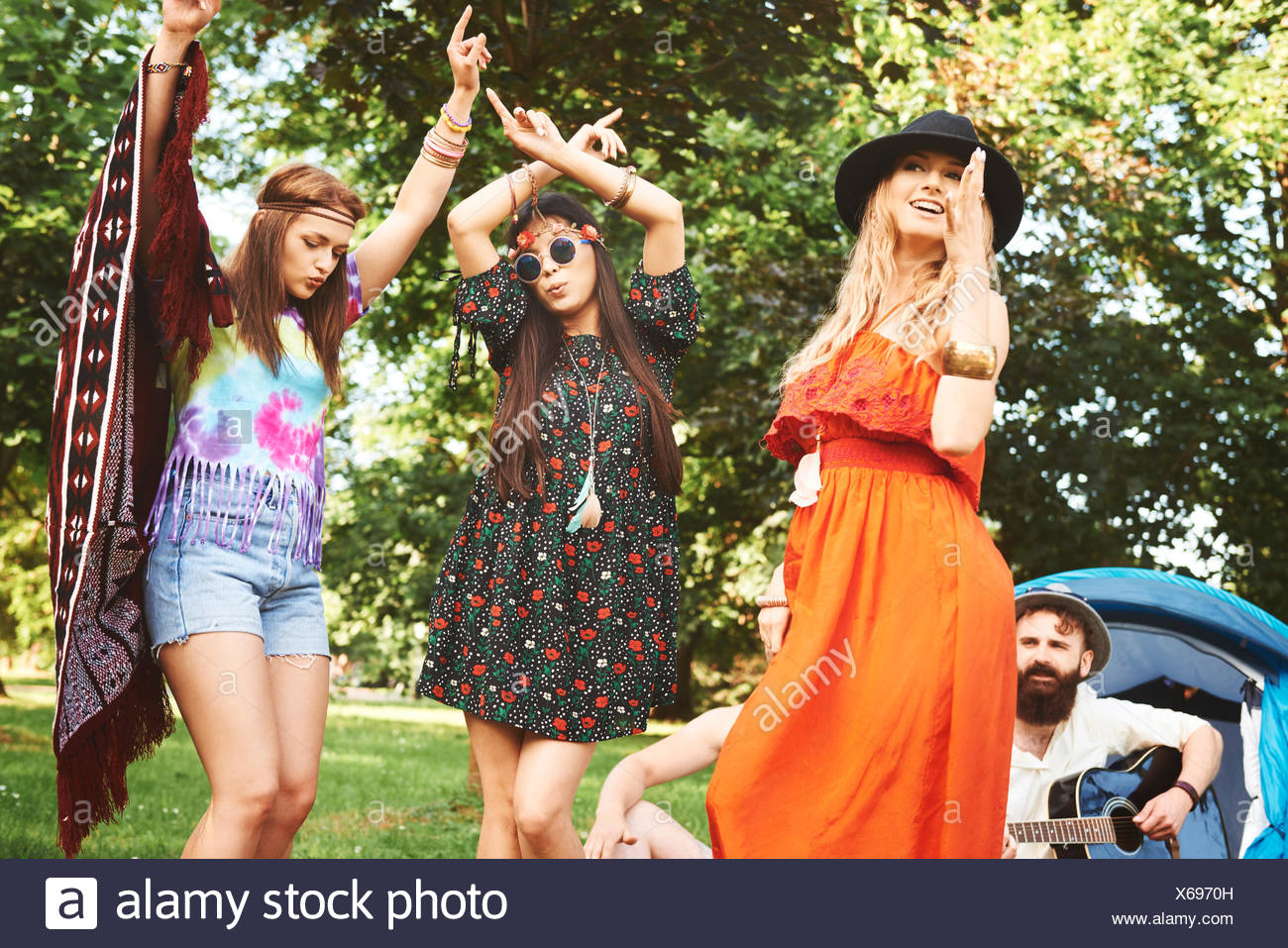 Three young boho women dancing together at festival - Stock Image