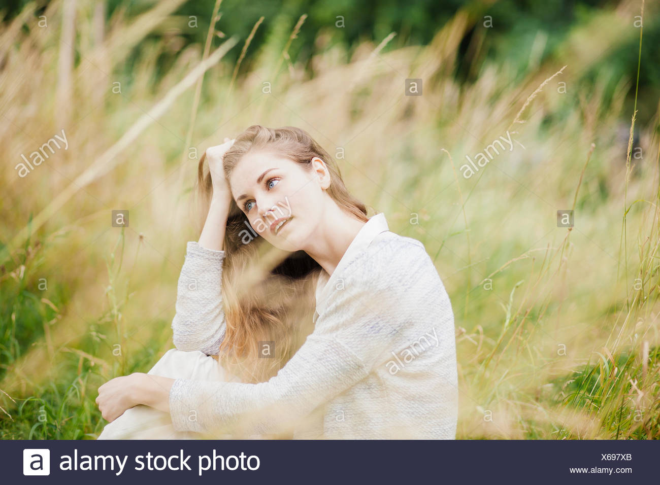 Young woman sitting in long grass with hand in hair - Stock Image