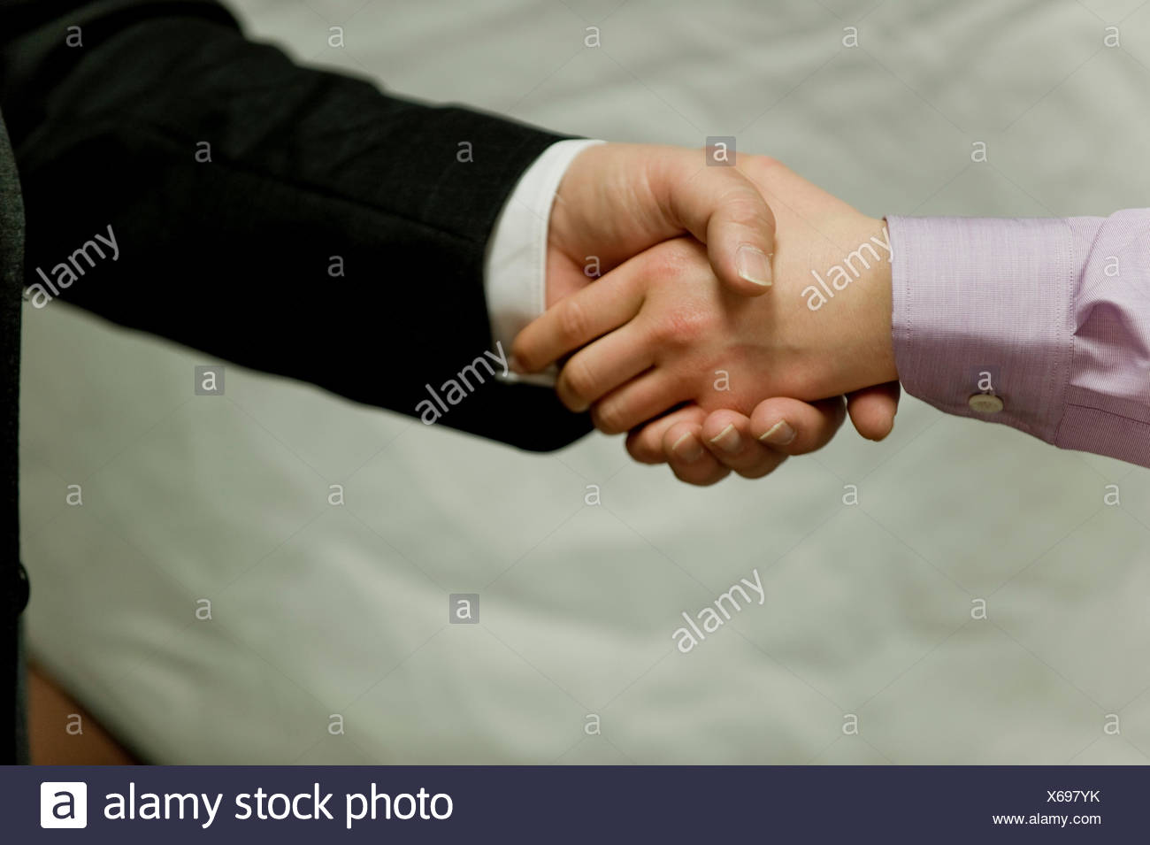 businesswoman and a businessman shaking hands - Stock Image