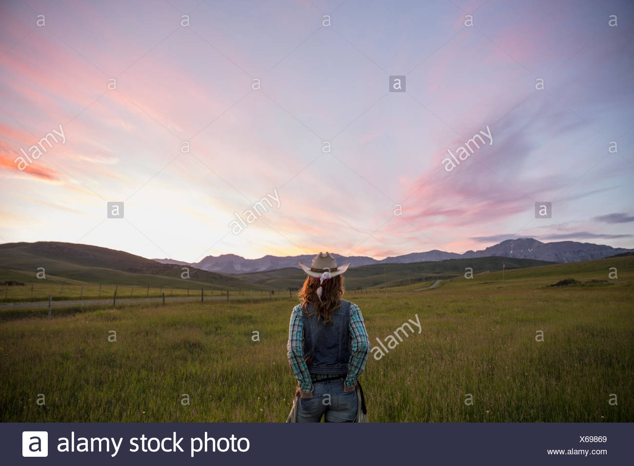 Female rancher watching dramatic sunset sky over field - Stock Image