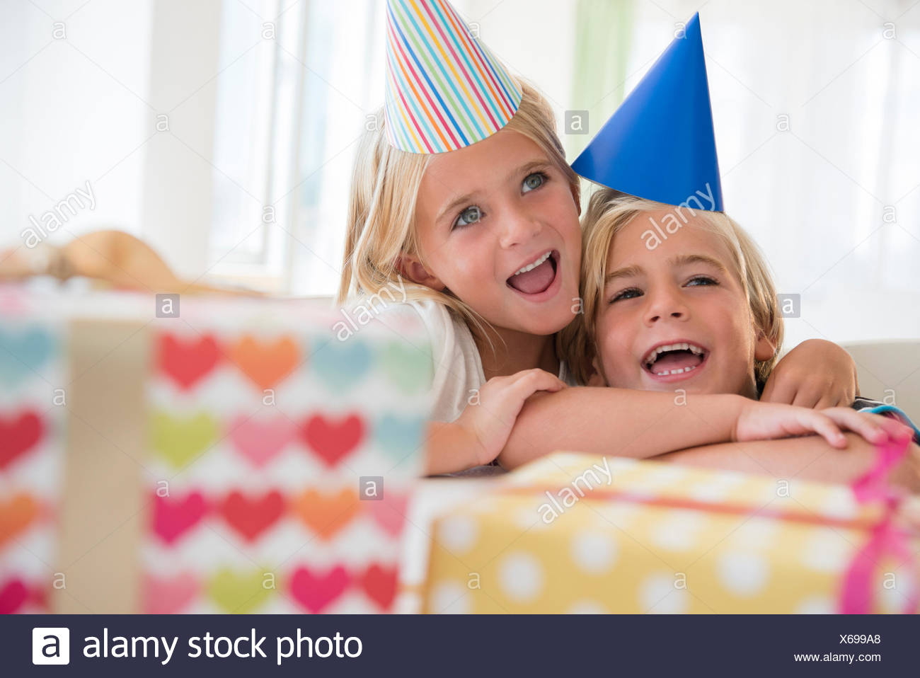 Brother (4-5) and sister (6-7) in embrace at birthday party - Stock Image