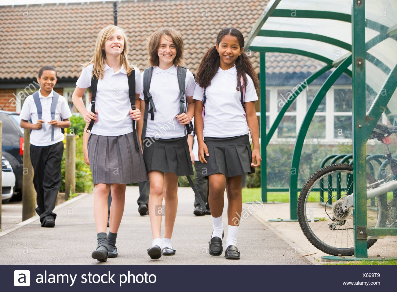 Three students leaving school with other students in background - Stock Image