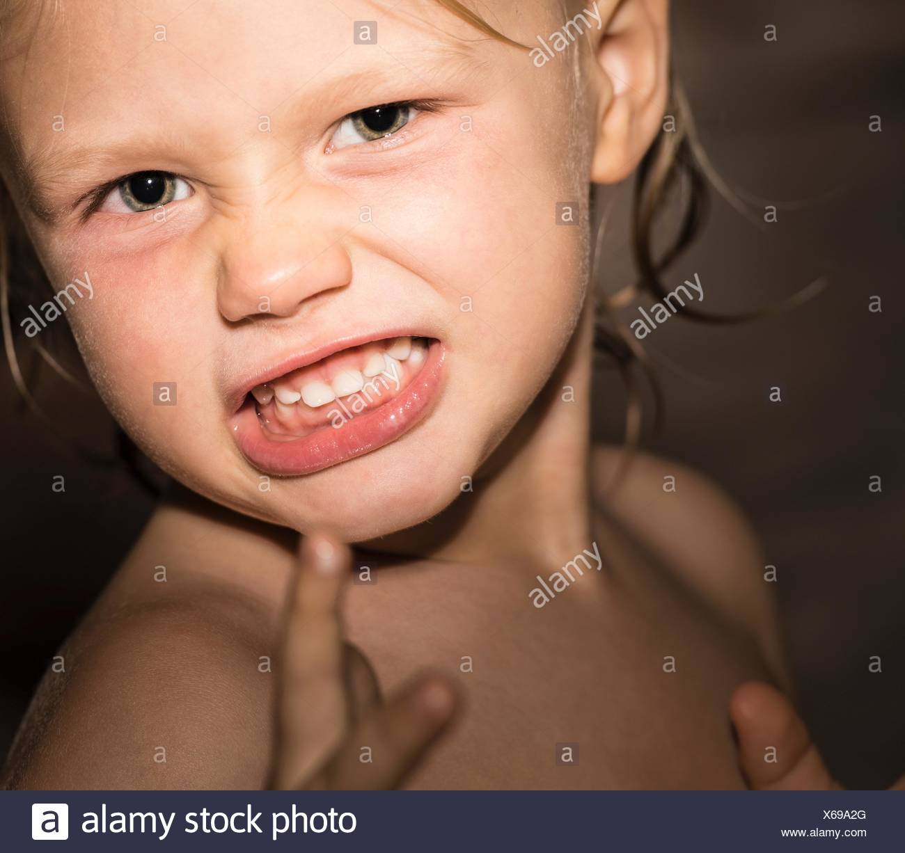 Close up portrait of aggressive boy with wet hair - Stock Image