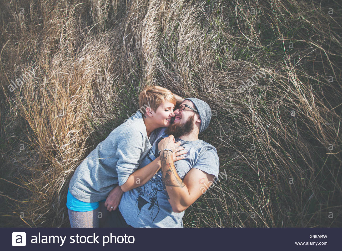 Elevated view of a couple lying on the grass - Stock Image