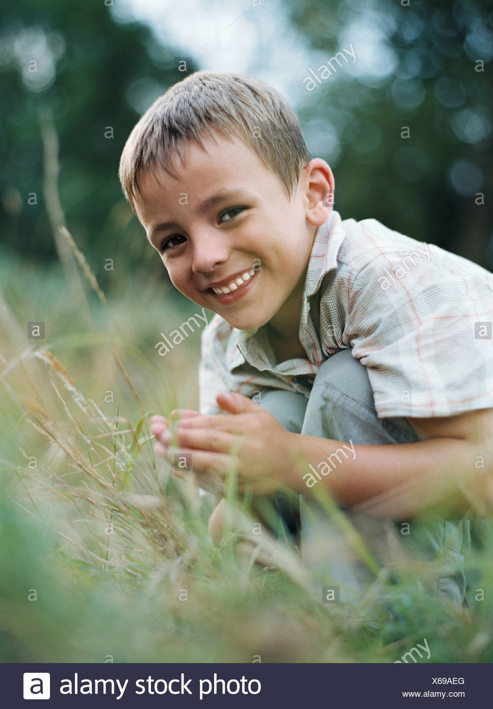 Boy crouching in grass - Stock Image