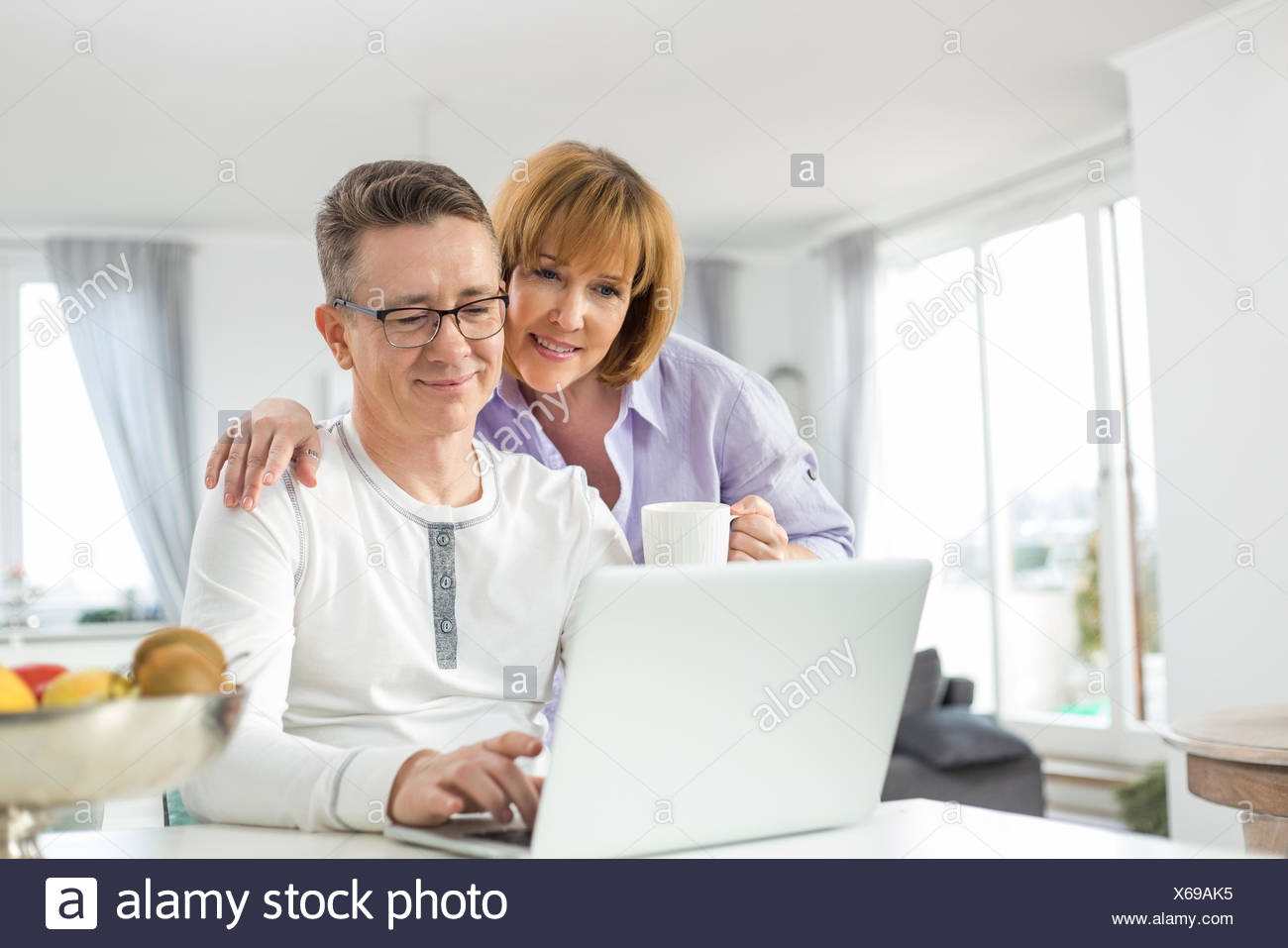 Loving couple using laptop together at home Stock Photo