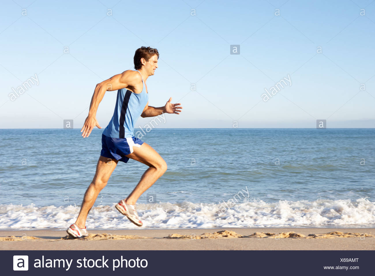 Young Man Fitness Clothing Running Along Beach - Stock Image