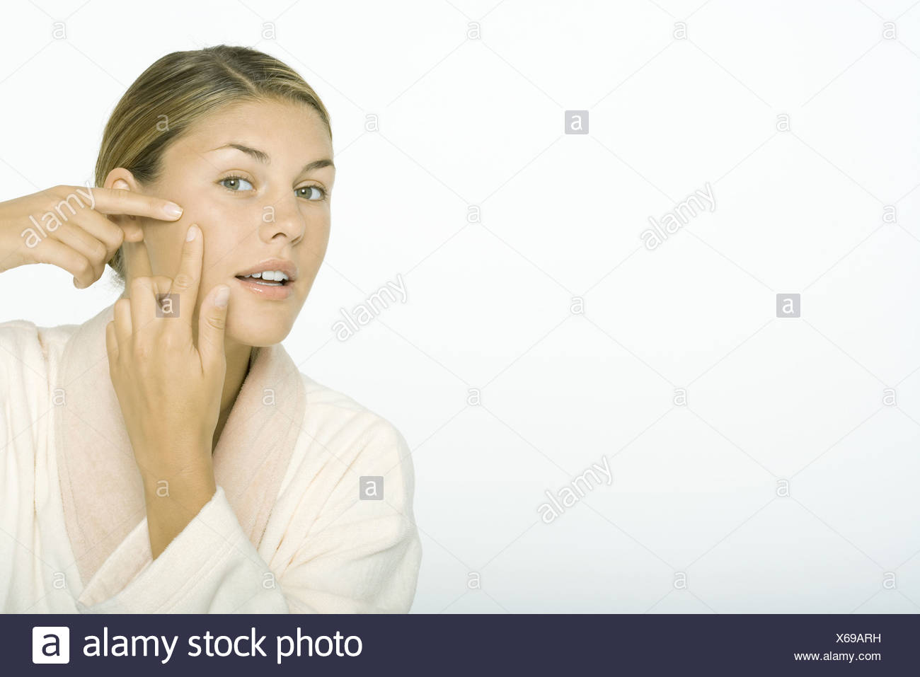 Young woman touching cheek with fingers - Stock Image
