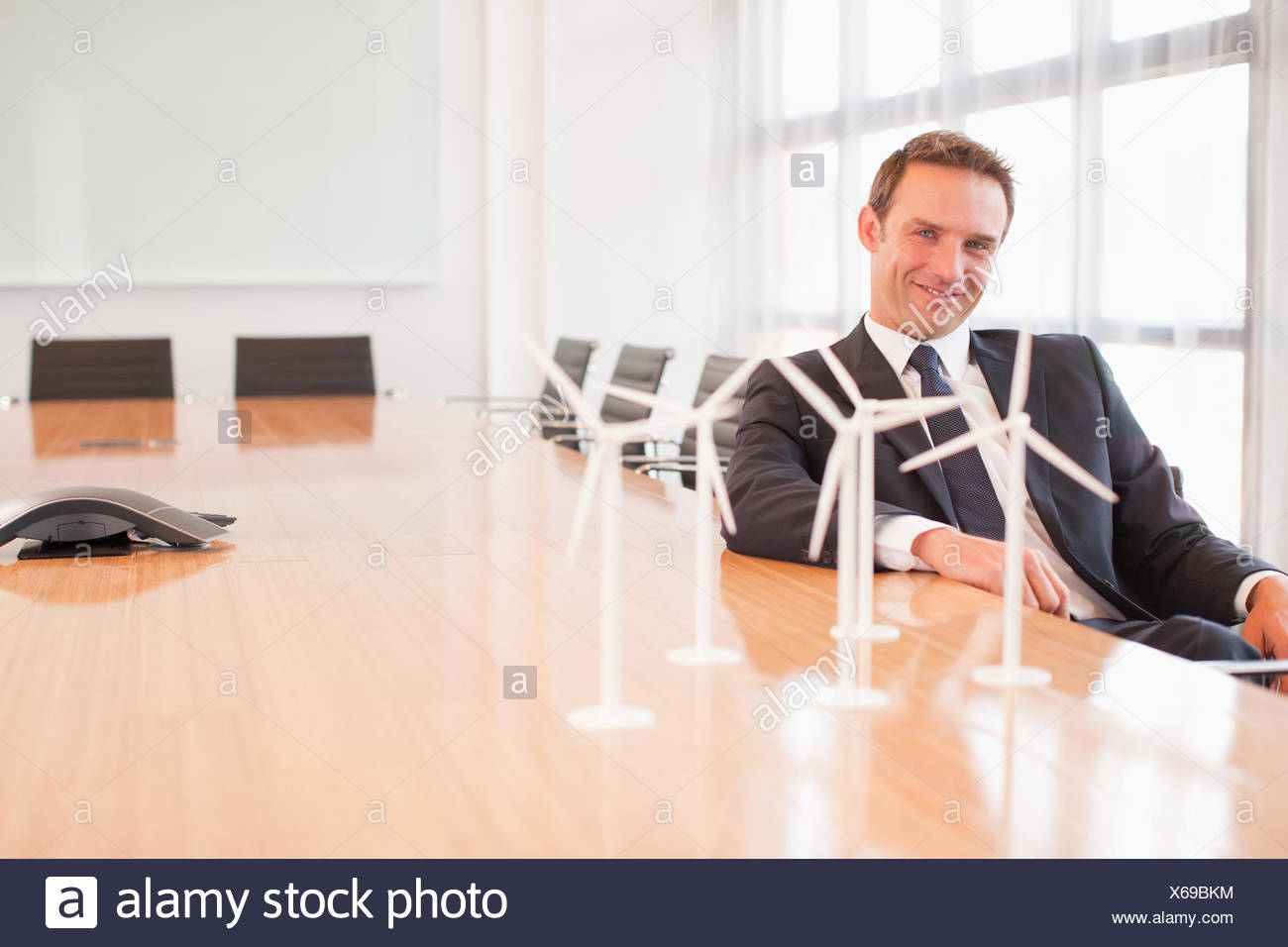 Businessman sitting with model wind turbines in conference room - Stock Image
