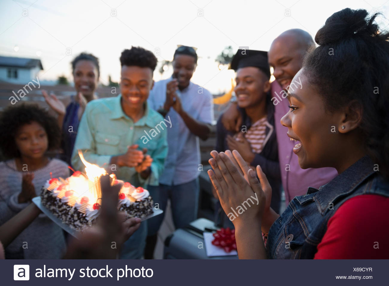 African American family celebrating graduation with cake - Stock Image