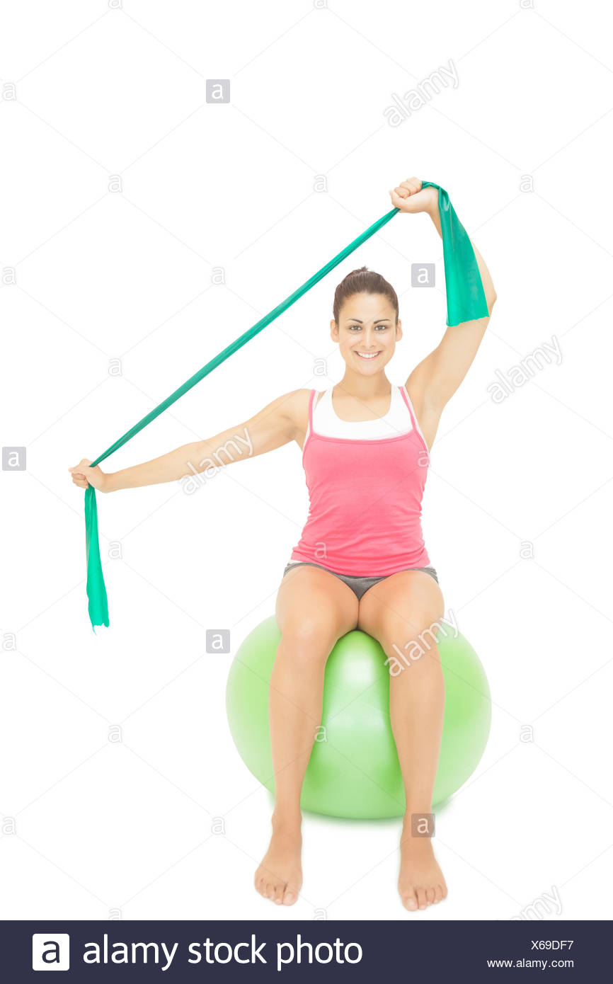 Gleeful sporty brunette stretching with resistance band - Stock Image