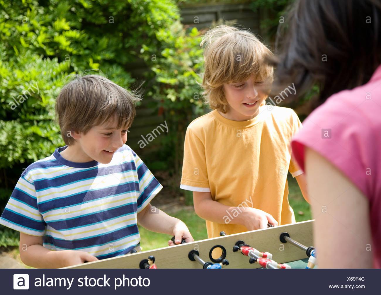 Two boys playing table football - Stock Image