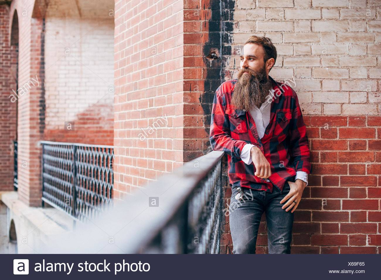 Man with beard leaning on balcony looking away - Stock Image
