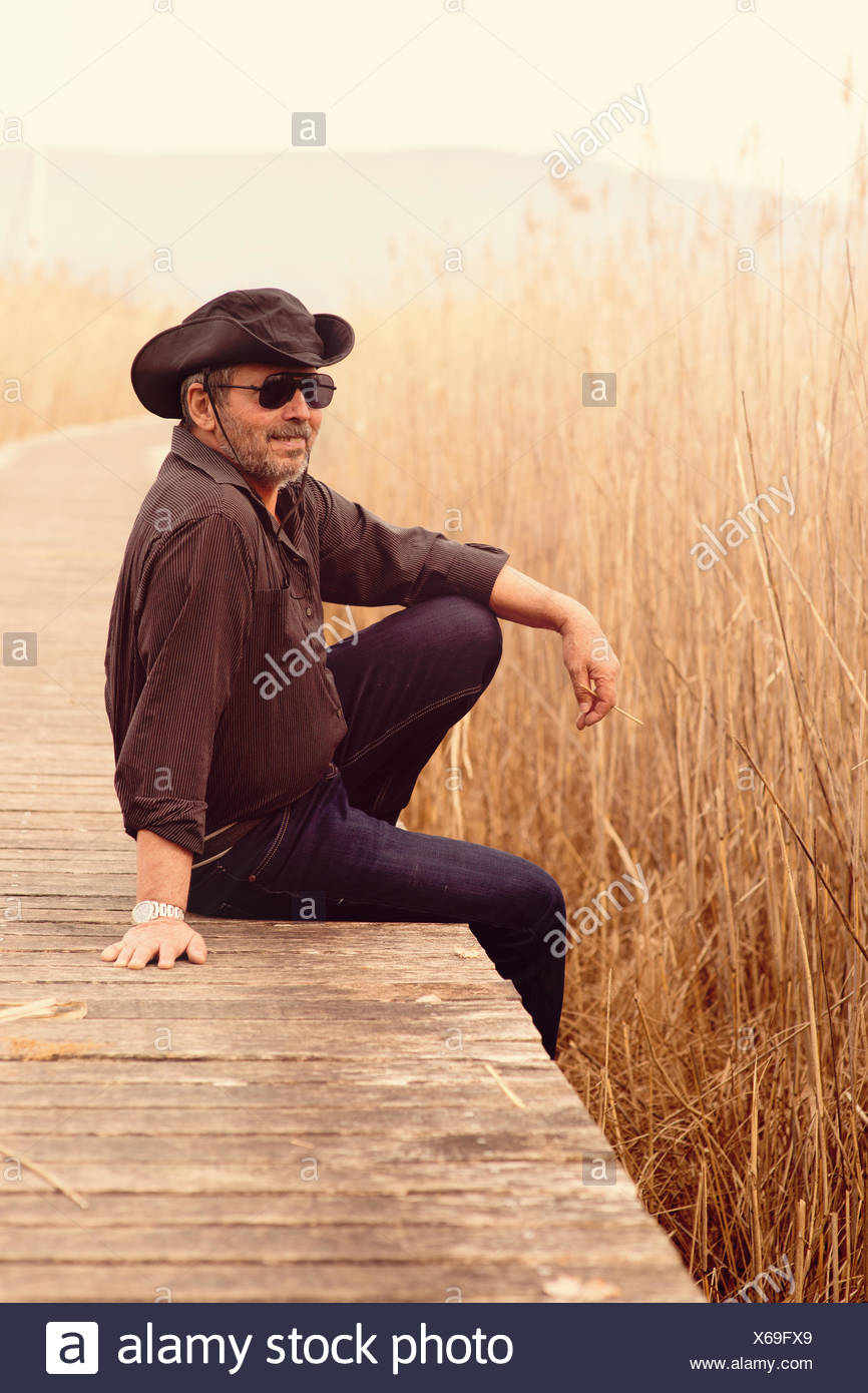 Portrait of senior man wearing sunglasses and cowboy hat sitting on edge of wooden footbridge - Stock Image