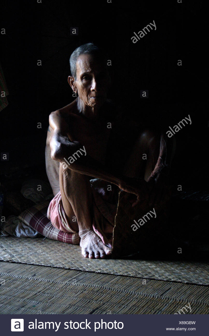 old man from Iban tribe sitting in the longhouse. Longhouse is a gigantic wooden  structures on stilts, where the entire - Stock Image