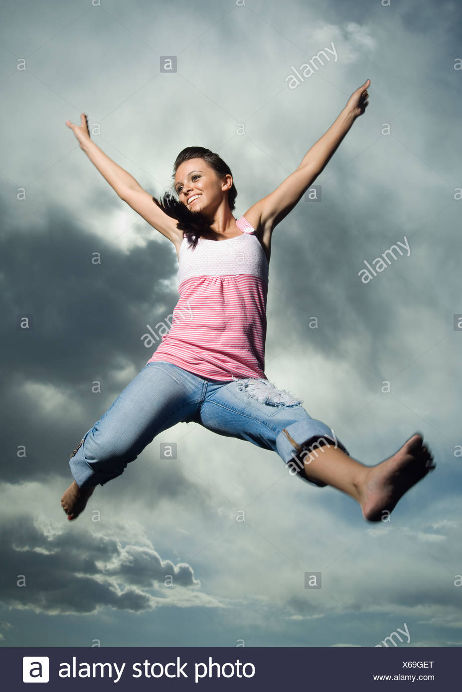 Low angle view of woman jumping - Stock Image
