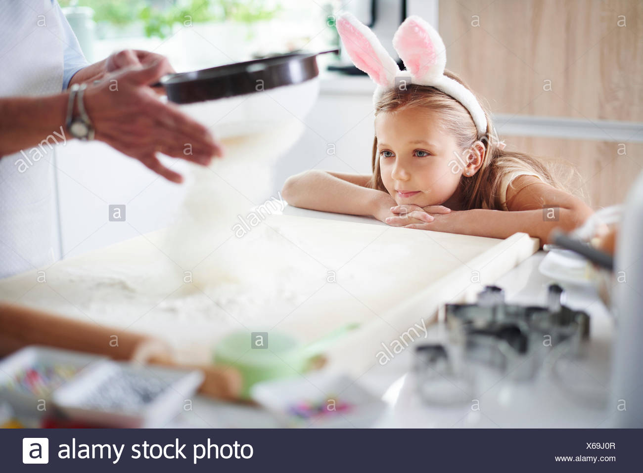 Girl watching grandmother sift flour for easter baking - Stock Image