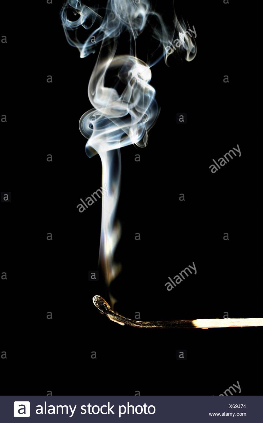Burnt matchstick on black background, close-up - Stock Image